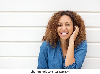 Closeup portrait of a beautiful woman laughing with hand in hair