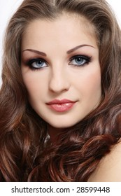 Close-up portrait of beautiful woman with long curly hair and smoky eyes