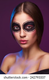 Closeup portrait of beautiful woman with painted art makeup. Natural beauty, clean fresh skin. Looking at camera. Inside