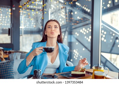 Closeup portrait of a beautiful woman puckering lips looking at camera holding cup of hot beverage. Hispanic girl wearing formal blue suit sitting at a table in a cafe or at home, near the window