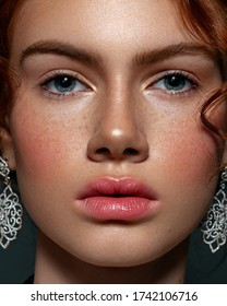 Close-up portrait of a beautiful woman with red hair. Strong skin texture with freckles. natural makeup, clean healthy skin.