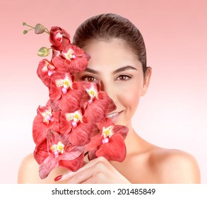 Closeup portrait of beautiful woman with red orchid flowers isolated on pink background, enjoying day spa, beauty treatment concept