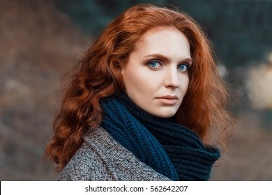 Closeup portrait of beautiful woman with red hair and blue eyes posing outdoors