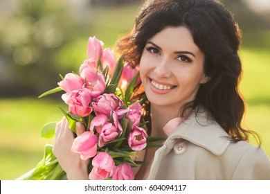 Closeup portrait of beautiful woman smiling with a braces holding bouquet of pink tulips and sitting in a park one spring day