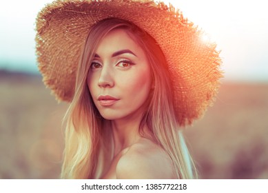 Closeup portrait, beautiful woman in straw hat. In the summer on the nature of the tanned girl with long hair. Emotions of tenderness, smile and relaxing in the fresh air.