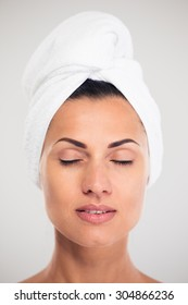 Closeup portrait of a beautiful woman with towel on head and closed eyes isolated on a white background