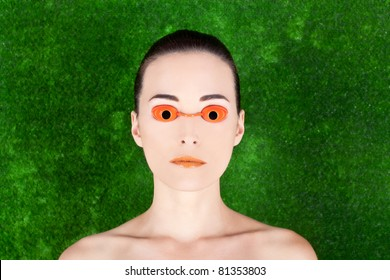 Closeup portrait of a beautiful woman wearing tanning bed glasses on green background