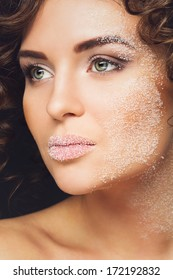 Closeup portrait of beautiful woman with white sugar on her face