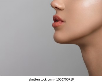 Close-up portrait of beautiful woman's purity face with nude lips make-up. Cute model with clean shiny skin and long neck. The place for your text, a gray background. Gives a kiss