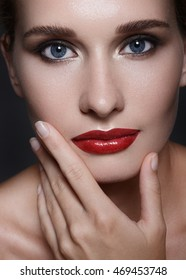 Close-up portrait of beautiful woman's purity face with red lips make-up. Cute model with clean shiny skin