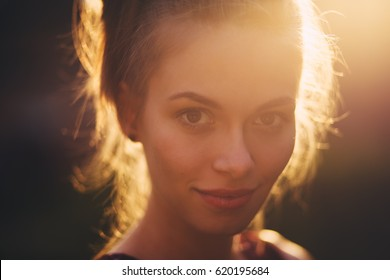 Close-up portrait of beautiful young adult woman in the sunlight at sunset. Pretty girl is smiling. She is cute and funny. Beautiful woman is enjoying warm and sunlight. She is basking in the sun
