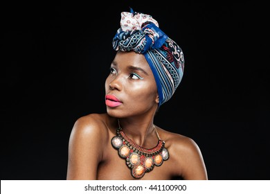 Close-up portrait of a beautiful young afro american woman looking away isolated on the black background