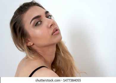 Closeup portrait of a beautiful young blonde with green eyes, white background. The face is half a turn, the head is thrown back. Place for text
