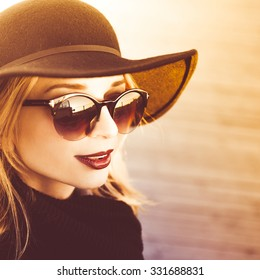 close-up portrait of a beautiful young blonde girl in stylish hat autumn in sunglasses with dark red full lips smiling at sunset on a sunny day and posing lifestyle in the city