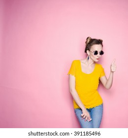 close-up portrait of a beautiful young blonde girl in fashionable sunglasses on a pink background in the studio in a yellow blouse and jeans holding a popular phone smiling