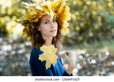 Close-up portrait of a beautiful young brunette woman with a wreath of yellow maple leaves on her head and in blue jersey. girl holds autumn maple leaves in hand. Golden park in the background.