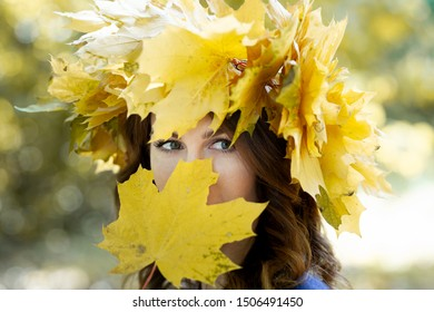 Close-up portrait of a beautiful young brunette woman with a wreath of yellow maple leaves on her head. girl covers all her face with a yellow maple leaf, except eyes. Golden park in the background.