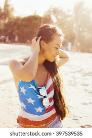 close-up portrait of a beautiful young brunette in sunglasses girl on a sunny day in the summer on the beach by the sea smiling at sunset in denim shorts and top with print US flag lifestyle