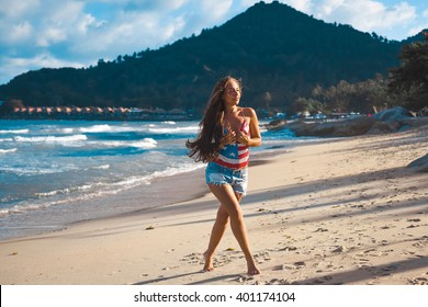 close-up portrait of a beautiful young brunette girl with long hair on a background of blue sea with waves and sky with clouds on a sunny day, lifestyle, posing and smiling, wind in the mountains