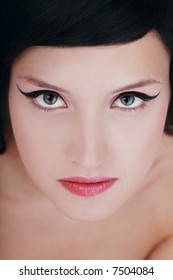 Close-up portrait of beautiful young brunette with trendy makeup