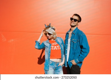 close-up portrait of a beautiful young couple on a sunny day, hipsters, girl blonde with red lips and wearing sunglasses and attractive guy with a beard  a denim jacket