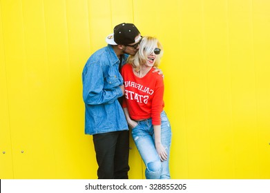 close-up portrait of a beautiful young couple in love bright blonde girl with red lips and a guy with a beard wearing a cap hipsters  yellow background smiling and posing lifestyle  telephone selfie