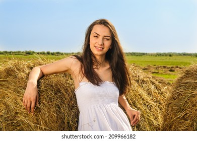 close-up portrait of a beautiful, young, emotional woman sitting next to haystack