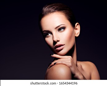 Closeup portrait of a beautiful young fashion woman with glamour makeup posing at studio isolated on white.