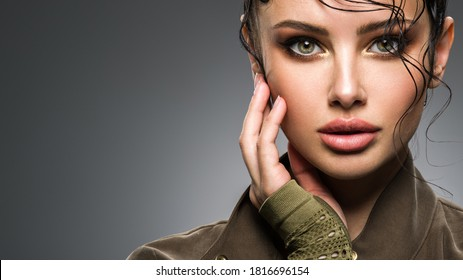 Closeup portrait of a beautiful young fashion woman with glamour makeup posing at studio. Portrait of an attractive woman in green clothes.