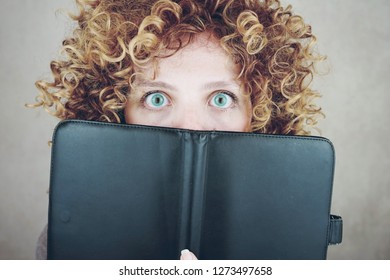 Close-up portrait of a beautiful and young funny woman with blue eyes and curly blonde hair, she is behind of a agenda or ebook and she is surprised
