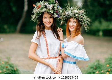 Closeup portrait of beautiful young girl in traditional Slavic dress with wreath of summer flowers. Ethno folk style cheerful female on abstract background in summer at floral feast. Expressive face