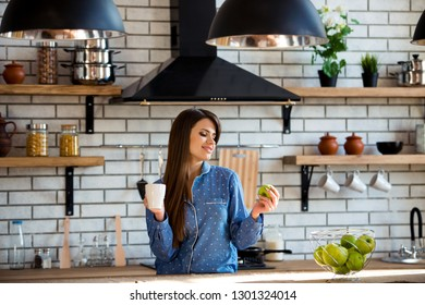 Closeup portrait of beautiful young girl with cup of tea or coffee in blue pajamas in the kitchen. Invigorating morning drinks for energy whole day