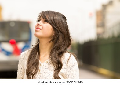 closeup portrait beautiful young girl walking in the streets af city looking up