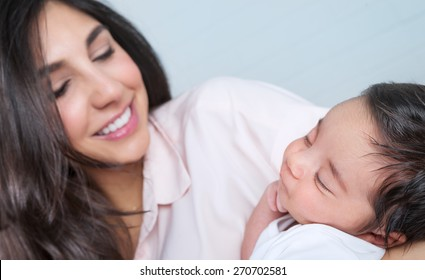 Closeup portrait of beautiful young happy mother having fun with her little newborn baby at home, enjoying first day of motherhood, love and happiness concept