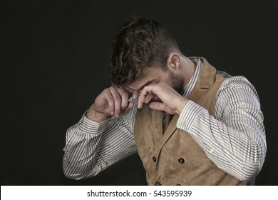 closeup portrait of the beautiful young man with a beard, crying, wiping tears hands