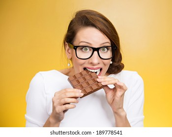 Closeup portrait, beautiful, young nerd woman with black glasses craving square milk chocolate isolated yellow background. Food diet option dilemma.