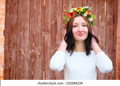Closeup portrait of beautiful young smile woman with flower wreath on her head near the wooden door. Beauty concept