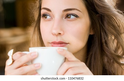 Closeup portrait of a beautiful young woman having coffee.