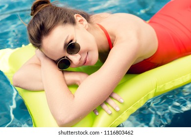 close-up portrait of beautiful young woman lying on inflatable mattress in swimming pool