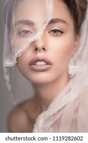 Closeup portrait of beautiful young woman with nude makeup and veil on face