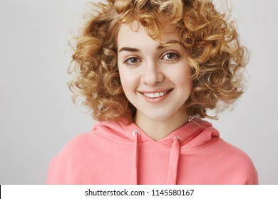 Close-up portrait of beautiful young woman with curls smiling friendly, looking confident and relaxed while taking interview during work, standing over gray background, posing for advertisement