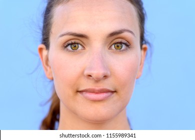 Closeup portrait of beautiful young woman with open eyes, light blue background.