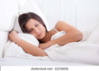 Closeup portrait of a beautiful young woman sleeping peacefully in her bed facing the camera