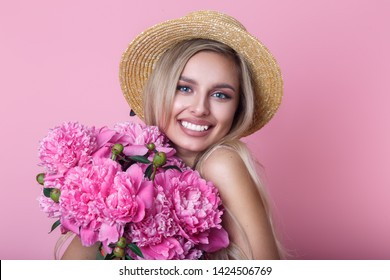 Close-up portrait of beautiful young woman in summer dress and straw hat holding peonies bouquet and looking over her shoulder over pink background