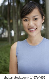 Closeup portrait of beautiful young woman smiling in park