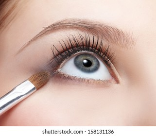 closeup portrait of beautiful young woman applying eye shades with cosmetic brush