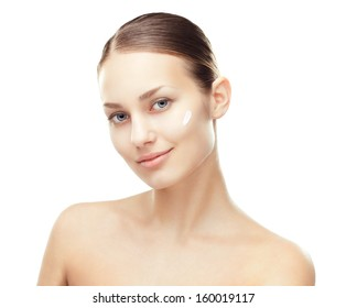 Closeup portrait of  beautiful young woman with cosmetic cream on a cheek isolated on white background