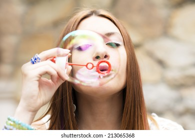 Closeup portrait of beautiful young woman inflating colorful soap, outdoor.