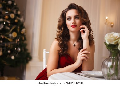 Close-up portrait of beautiful young woman in gorgeous red velvet evening dress sitting by the table in expensive interior