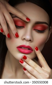 Closeup portrait of beautiful young woman with bright red eyeshadows, lips and nails